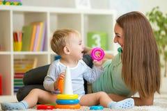 Nette Mutter und Baby spielen zusammen Innen an Lizenzfreies Stockbild