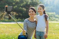 Nette Mutter und Tochter, die draußen ein selfie nimmt Stockbilder