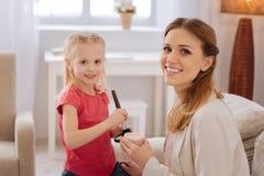 Nette nette Mutter und Tochter, die eine Make-uplektion hat Stockbild