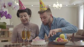 Nette Oma und erwachsener Enkel, die am Tisch mit Geburtstagskappe auf ihren Köpfen sitzt Der Mann, der einen Kuchen, Frau schnei stock video