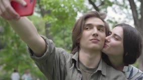 Nette Paare des Portr?ts von den Studenten, die das selfie sitzt auf dem Gras im Park nehmen Der Kerl ist im Vordergrund, das M?d stock video footage