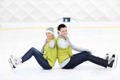 Nette Paare, die auf der Eisbahn sitzen stockbilder