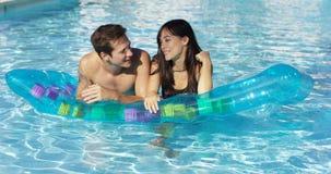 Nette Paare, die auf sich hin- und herbewegender Matratze im Pool sich entspannen stockfotos