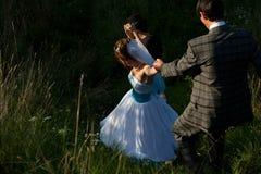Nette Paare, die den Weg in den Kräutern und im Gras hinuntergehen Lizenzfreies Stockfoto