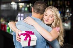 Nette Paare, die ein Geschenk habend umarmen Stockbilder