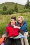 Nette Paare, die eine Pause auf einer Wanderung machen, um Karte mit dem Frauenzeigen zu betrachten Lizenzfreie Stockfotografie