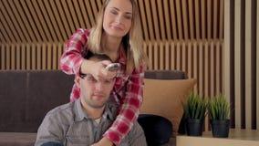 Nette Paare, die im Wohnzimmer fernsehen stock footage