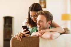 Nette Paare, die Smartphone auf Couch betrachten lizenzfreies stockbild