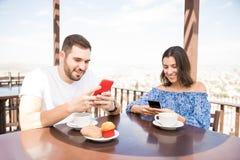 Nette Paare, die Spaß unter Verwendung des Smartphone zur Frühstückszeit haben stockbilder
