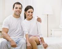 Nette Paare, die zusammen in ihrem Schlafzimmer sitzen Lizenzfreie Stockbilder