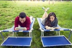 Nette Paare entspannen sich auf deckchair Lesebuch und -tablette Stockbilder