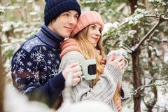 Nette Paare mit heißem Tee in den Schalen im Wald unter Tannenbäumen Lizenzfreies Stockbild