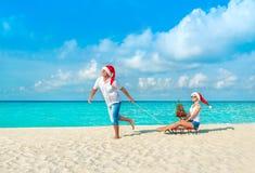 Nette Paare in roten Sankt-Hüten, die am sandigen Strand des tropischen Ozeans mit Schlitten, verziertem Tannenbaum und Geschenkb stockbild
