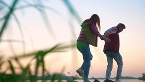 Nette Paarmann-Holdinghand seiner Freundin und auf Steine sorgfältig gehen, während Wasser sie umgibt, Natur stock video footage