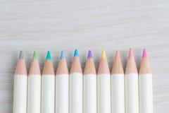 Nette Pastellfarbe zeichnet auf hellgrauem hölzernem Hintergrund mit c an Lizenzfreie Stockbilder