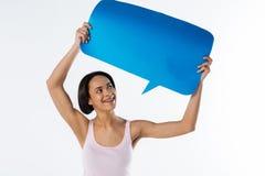 Nette positive Frau, die das blaue Zeichen betrachtet Stockbild
