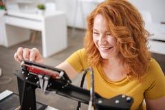 Nette positive Frau, die den Monitor des Druckers 3d betrachtet Stockfotos