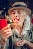 Nette positive Frau, die ihre Zunge zur Kamera zeigt stockfoto