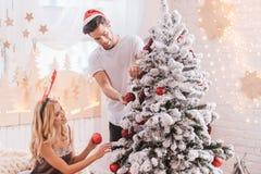 Nette positive Paare, die den Weihnachtsbaum verzieren Stockfoto