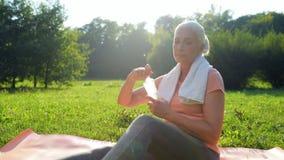 Nette positive sportliche Frau, die nach Sport im Park stillsteht stock video