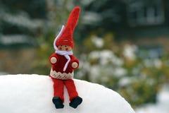 Nette Puppe, die im Schnee sitzt Lizenzfreie Stockbilder