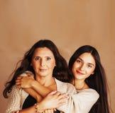 Nette recht jugendlich Tochter mit der reifen umarmenden Mutter, Modeart Brunette-Make-upabschluß herauf tann Mulatten, warme Far lizenzfreie stockbilder