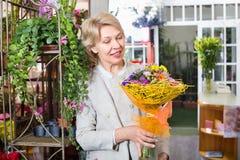 Nette reife blonde Frau, die Blumen vorwählt stockfotografie