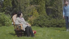 Nette reife Dame des Portr?ts, die auf dem Rasen im Schaukelstuhl genie?t Sonne sitzt Erwachsener Enkel, der mit Wasser kommt stock video