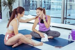 Nette reife Frau, die auf Yogatrainer hört stockfoto