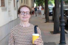 Nette reife Frau, die draußen Kaffeetasse hält lizenzfreie stockbilder