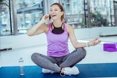 Nette reife Frau, die am Telefon während des Trainings plaudert stockfotos