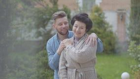 Nette reife Frauenstellung des Porträts im Garten vor dem großen Haus, erwachsener Enkel, der sie, Setzen umarmt stock footage