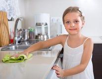 Nette Reinigung des kleinen Mädchens an der Küche Stockfotos