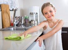Nette Reinigung des kleinen Mädchens an der Küche Lizenzfreie Stockbilder