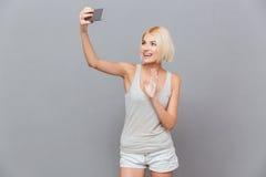 Nette reizende junge Frau, die selfie unter Verwendung des Handys nimmt Lizenzfreie Stockbilder