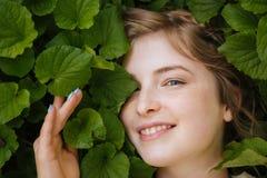 Nette reizende junge Frau mit grünen Blättern lizenzfreie stockfotografie