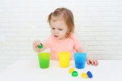 Nette reizende kleine 2 Jahre Mädchen sortiert Details durch Farbe Stockbilder