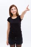 Nette reizende nette junge Frau, die weg schaut und zeigt stockfotografie