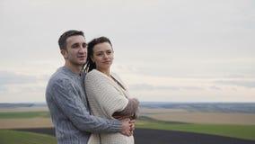 Nette reizende Paare stehen in den Umarmungen auf dem Abgrund eines Felsens 4K stock footage