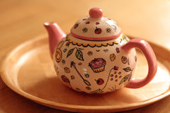 Nette rosafarbene Teekanne auf Tabelle Stockbild