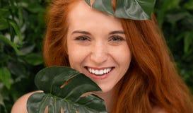 Nette Rothaarigefrau, die durch monstera Blätter lacht stockfoto