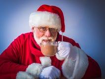 Nette Santa Claus mit glas der köstlichen Kakaos zu Hause Stockfotografie