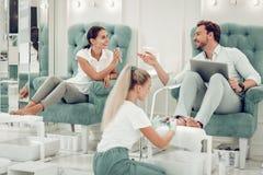 Nette schöne beim Sitzen aktiv sprechende Paare in den Lehnsesseln lizenzfreie stockfotografie