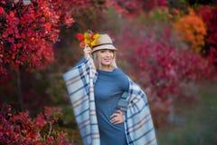 Nette schöne Mädchendamenfrau mit dem blonden Haar im stilvollen Kleid mit dem Hut, der im Herbstwald steht stockfotos