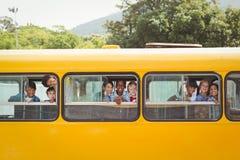 Nette Schüler, die an der Kamera im Schulbus lächeln Lizenzfreie Stockbilder