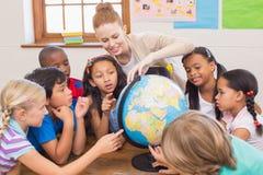 Nette Schüler und Lehrer im Klassenzimmer mit Kugel stockbilder