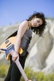 Nette schauende junge Frau, die mit Gitarre aufwirft Lizenzfreie Stockbilder