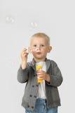 Nette Schlagblasen des kleinen Jungen auf Grau Stockbild