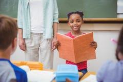 Nette Schüler, die an der Kamera im Klassenzimmer lächeln Lizenzfreie Stockfotografie