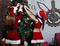 Nette Schnee-Mädchen kleiden oben den Baum des neuen Jahres Stockfotos